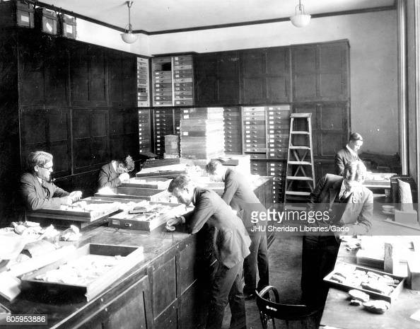 Prominent paleobotanist and professor Edward Wilber Berry and students in his class examine specimens in a laboratory in Latrobe Hall an academic...
