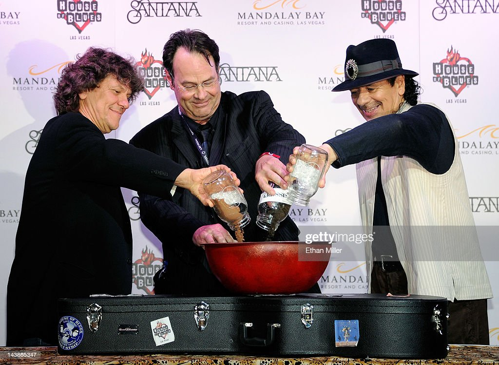 Promoter and co-founder of the original Woodstock Music & Art Fair Michael Lang, actor and House of Blues co-founder Dan Aykroyd and recording artist Carlos Santana pour dirt into a bowl at the House of Blues inside the Mandalay Bay Resort & Casino during a mud ceremony May 4, 2012 in Las Vegas, Nevada. The ceremony involved combining dirt from the town of Clarksdale in the Mississippi Delta with dirt from Bethel, New York from the site of the Woodstock Festival and mud from Santana's hometown of Autlan de Navarro, Jalisco in Mexico to symbolize his two-year residency at the music venue.