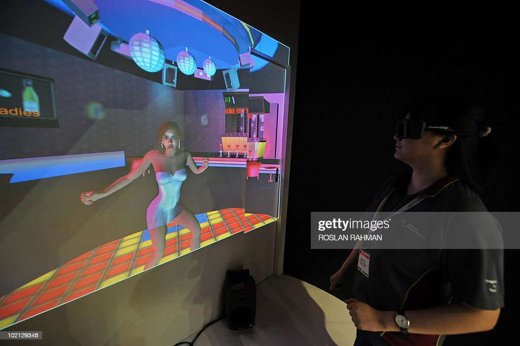 A promoter dances with a syncronised 3-D virtual dancer at the CommunicAsia 2010 conference and exhibition show in Singapore on June 16, 2010. The exhibition showcases the newest technologies, products and solutions, featuring almost 2000 exhibiting companies from 57 countries and region.