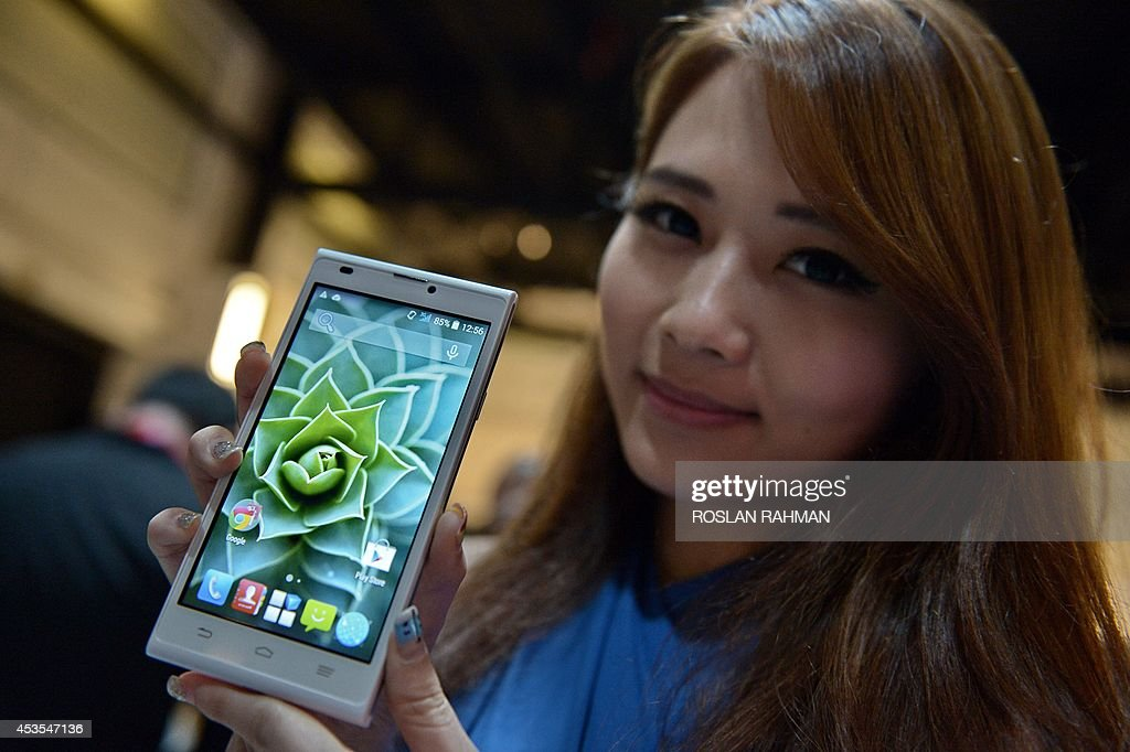 A promoter display one of the latest smart phones from ZTE, the Blade L2, during its launch in Singapore on August 13, 2014. The Chinese telecoms giant is among a growing number of Asian brands that are challenging the dominance of Apple and Samsung with high-spec low-price phones.