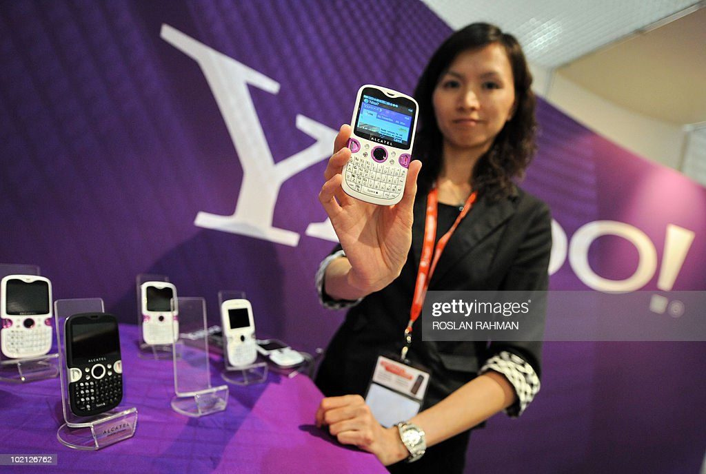 A promoter displays the yahoo application on an Alcatel smartphone at the CommunicAsia 2010 conference and exhibition show in Singapore on June 15, 2010. Mobile phone applications are one of the growth areas for the telecom sector, thanks in large part to the success of the iPhone.