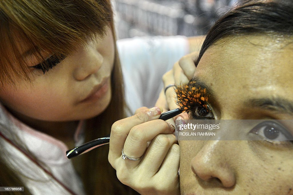 A promoter fixes an eye-lash for a customer during a demonstration at the BeautyAsia show in Singapore on February 27, 2013. The three-day BeautyAsia 2013 event showcases the latest innovations and trends in the beauty industry, which organisers said is one of the most 'recesssion-proof' sectors of the economy.