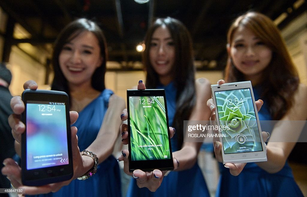 Promoters display the latest smart phones from ZTE, the KIS 3 (L), Blade VEC 4G (C) and the ZTE Blade L2 (R) during their launch in Singapore on August 13, 2014. The Chinese telecoms giant is among a growing number of Asian brands that are challenging the dominance of Apple and Samsung with high-spec low-price phones.