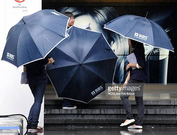 Promoters for the Royal Bank of Scotland stand outside a train station to hand out phamplets for its promotion on Time Deposit interest rates in...