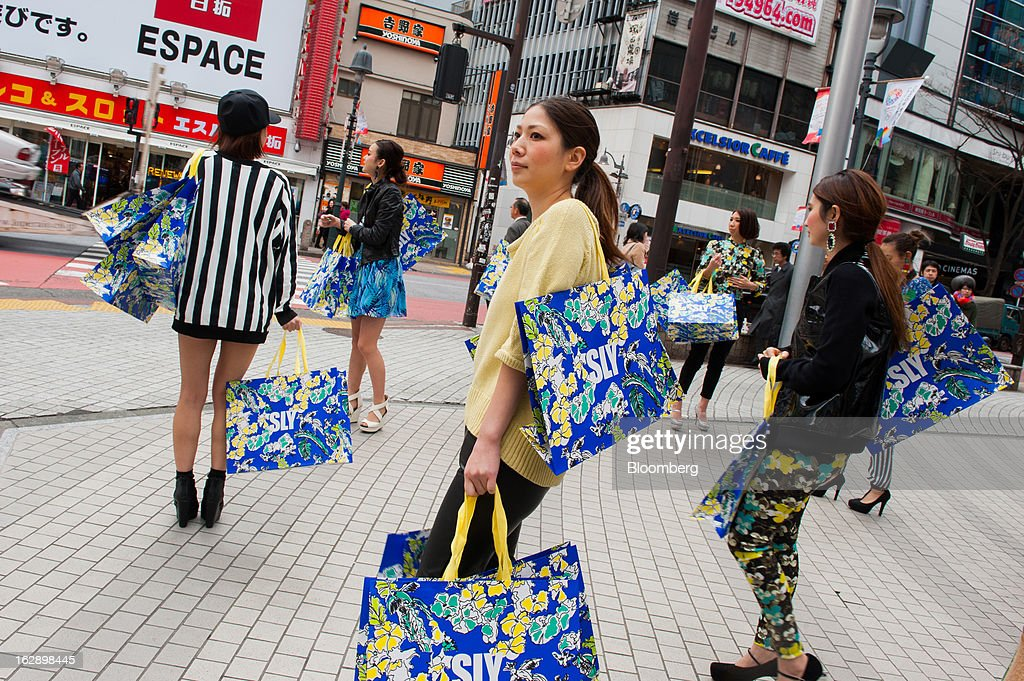 Promoters for the store 'Sly' carry branded shopping bags in the area of Shibuya in Tokyo, Japan, on Friday, March 1, 2013. Japan's consumer prices fell for the eighth time in nine months, highlighting the challenges facing the Bank of Japan in reaching a 2 percent inflation target. Photographer: Noriko Hayashi/Bloomberg via Getty Images