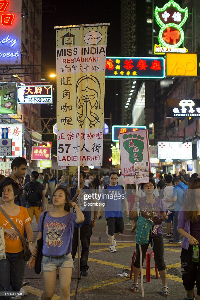 Promoters hold advertisements as pedestrians walk by in the Mong Kok district of Hong Kong, China, on Sunday, June 30, 2013. Hong Kongs best-selling newspapers called on readers to join a march to mark the anniversary of the citys handover to China, saying the government has failed to address issues of poverty and universal suffrage. Photographer: Jerome Favre/Bloomberg via Getty Images