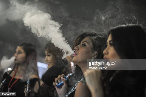 Promoters smoke electronic cigarettes during the VapeFair in Kuala Lumpur on December 5 2015 Vaping is an alternative to smoke by inhaling water...