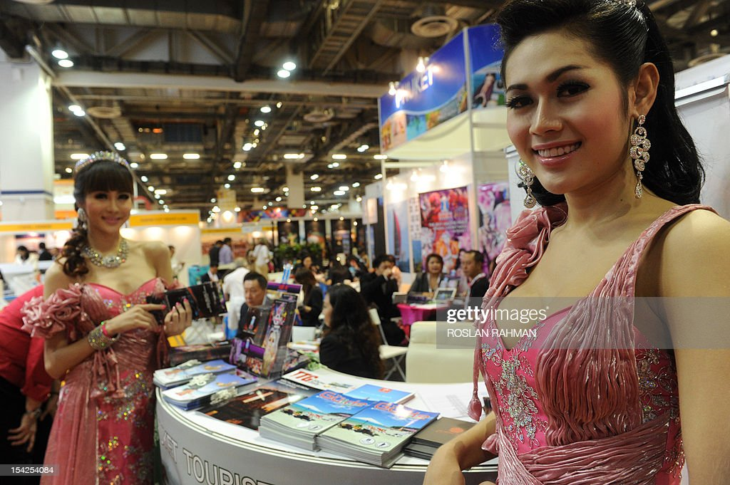 Promotion girls stand at a Phuket Tourist Association booth during ITB Asia, the trade show for Asian travel, in Singapore on October 17, 2012. More than 700 exhibitors from over 90 countries participate in the three-day trade event from October 17-19. AFP PHOTO / ROSLAN RAHMAN