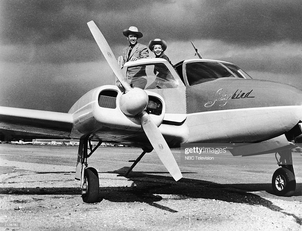 Promotional American actors Kirby Grant (1911 - 1985) and Gloria Williams leaning out of a Cessna 310G airplane for the television show, 'Sky King,' 1951.
