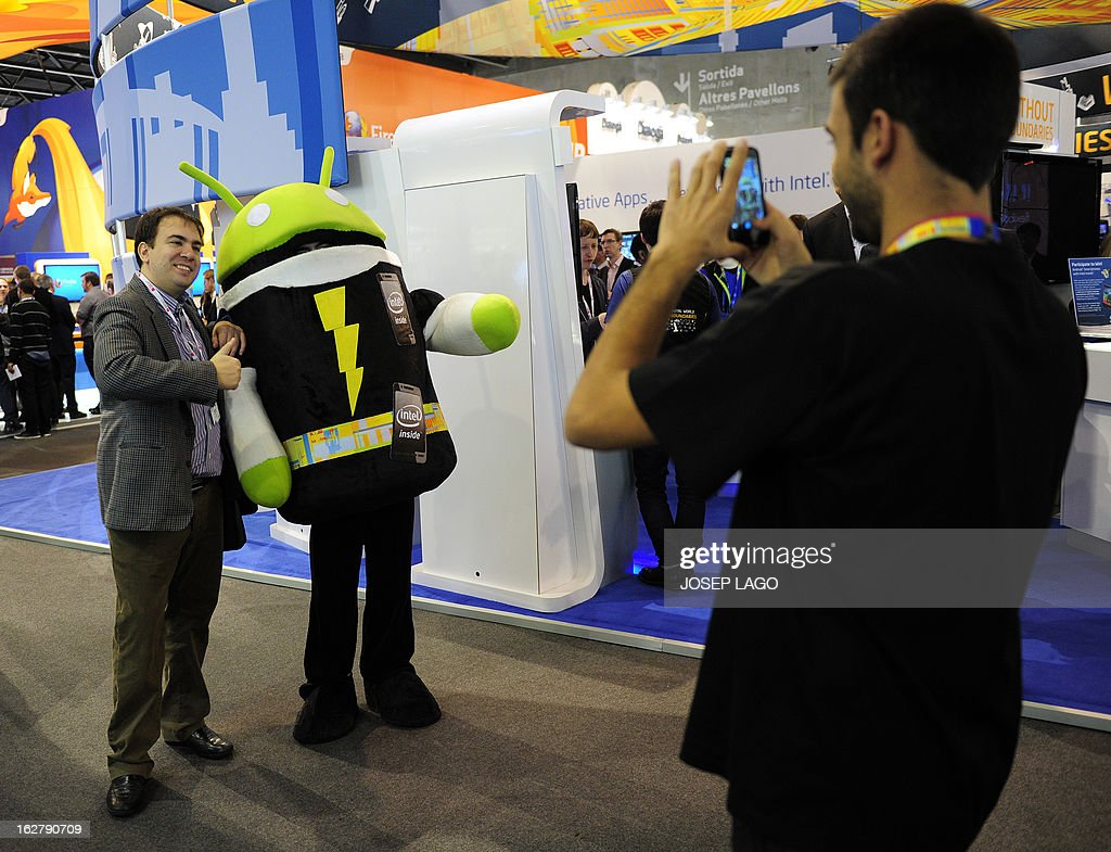 A promotional Android operating system character greets on February 27, 2013 a visitor at the Mobile World Congress, the world's biggest mobile fair, in Barcelona. The European Union warned member states on February 26 to free up the airwaves for new, super-fast fourth generation mobile networks and threatened legal action against those that deliberately block the process. AFP PHOTO/JOSEP LAGO