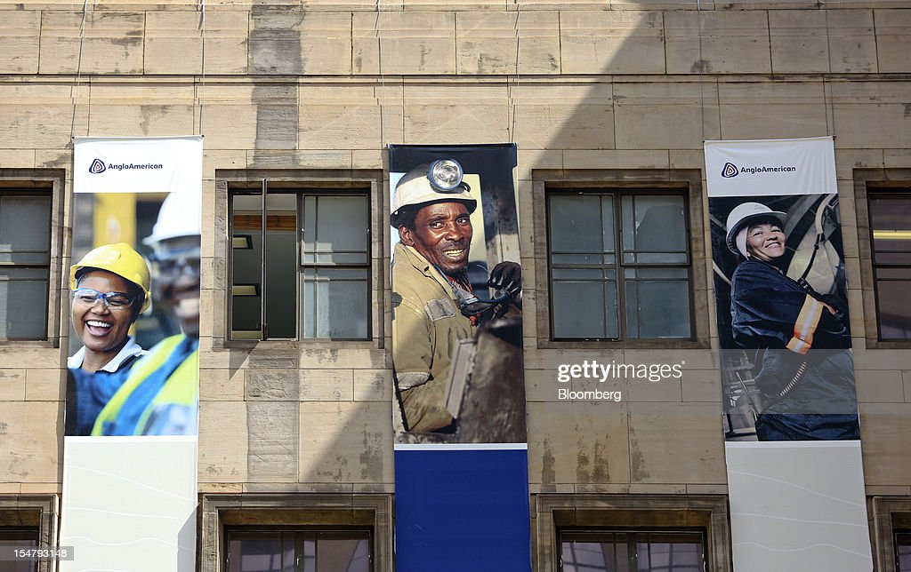 Promotional banners with photographs of employees at work hang from the offices of Anglo American Plc stand in the Marshalltown district of Johannesburg, South Africa, on Friday, Oct. 26, 2012. Anglo American Plc Chief Executive Officer Cynthia Carroll , the first woman, external hire and non-South African to hold the job, will quit after Anglo lost $14 billion in value in the more than five years she was in charge. Photographer: Chris Ratcliffe/Bloomberg via Getty Images
