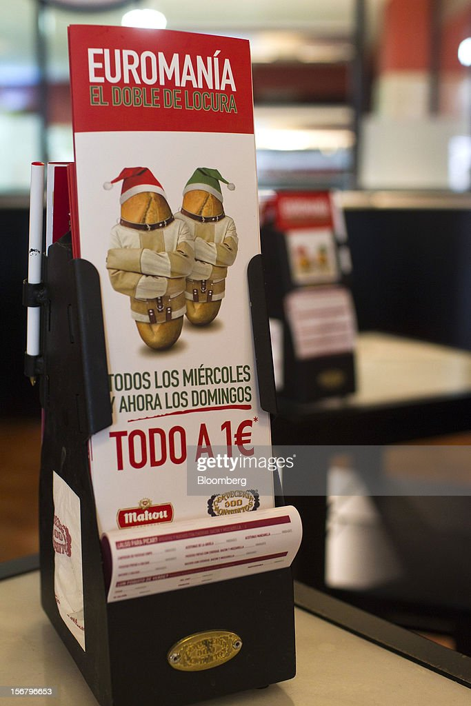Promotional cards advertising one euro menus as part of 'Euromania' Wednesdays stand on tables in a 100 Montaditos restaurant in Madrid, Spain, on Wednesday, Nov. 21, 2012. The Madrid-based chain in January opened its first U.S. restaurant in Miami and aims to have eight outlets in Florida by next March. Photographer: Angel Navarrete/Bloomberg via Getty Images