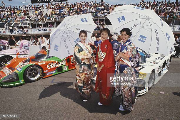 Promotional models dressed in traditional Japanese Geisha costume stand before the Mazdaspeed Co Mazda 787's on the grid before the FIA World...