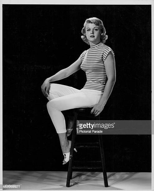 Promotional portrait of actress Angela Lansbury wearing white trousers and a striped blouse 1955