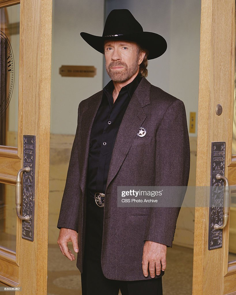 Promotional portrait of American actor Chuck Norris (as as Cordell 'Cord' Walker), dressed in a blazer over a black satin shirt and a black stetson, as he poses in a doorway for the television series 'Walker, Texas Ranger,' 1997.