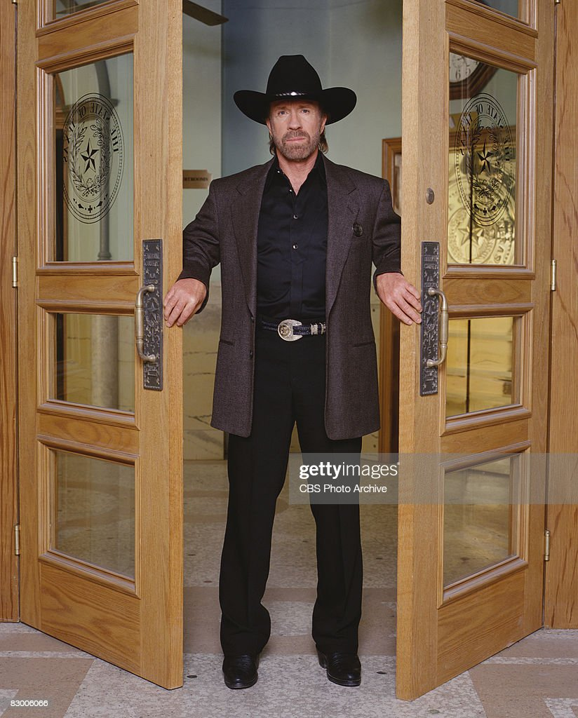 Promotional portrait of American actor Chuck Norris (as as Cordell 'Cord' Walker), dressed in a blazer over a black satin shirt and a black stetson, as he poses between two open doors for the television series 'Walker, Texas Ranger,' 1997.
