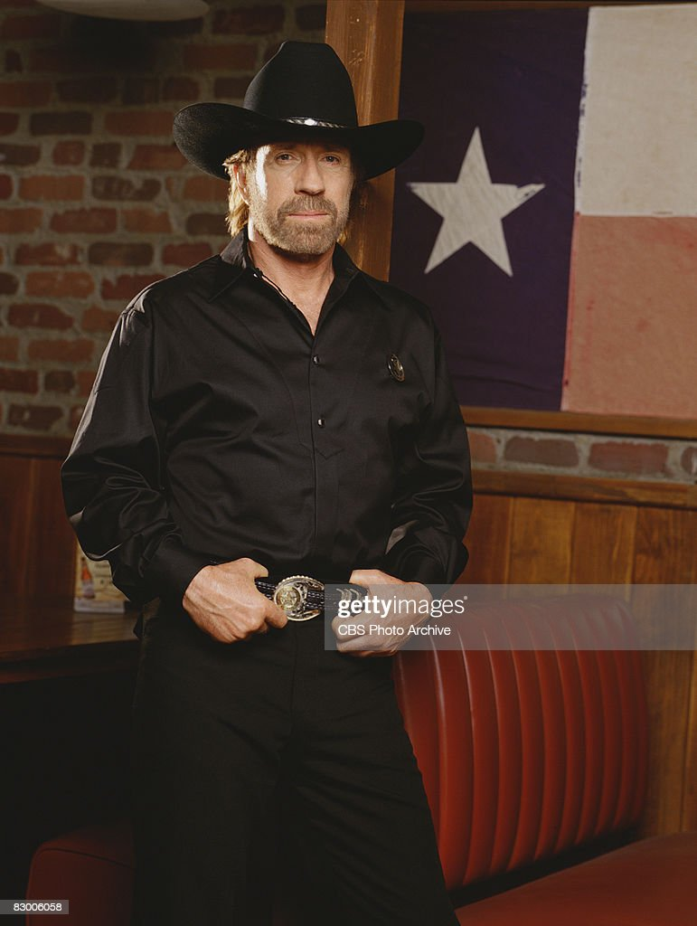 Promotional portrait of American actor Chuck Norris (as as Cordell 'Cord' Walker), dressed in a black satin shirt and a black stetson, as he poses with his hands on his belt for the television series 'Walker, Texas Ranger,' 1997.