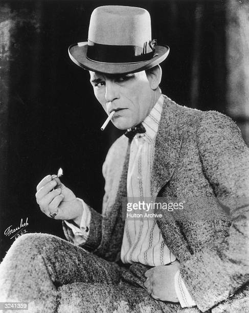 Promotional portrait of American actor Lon Chaney lighting a cigarette in his role for director Tod Browning's film 'Outside the Law' He wears a bow...