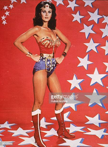 Promotional portrait of American actor Lynda Carter in costume in front of a backdrop of stars for the television series 'Wonder Woman' 1976