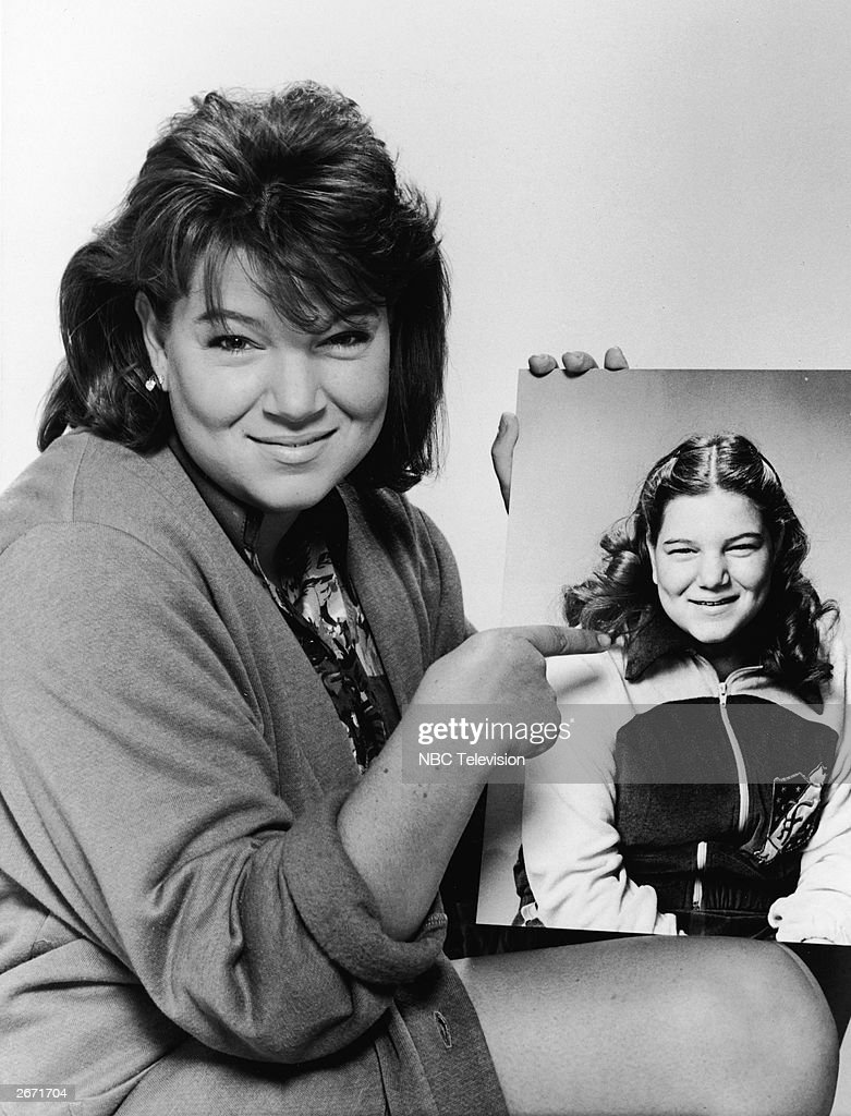 A promotional portrait of American actor Mindy Cohn pointing to a publicity picture of herself from 1979, the year the television series 'The Facts Of Life' premiered, 1985.