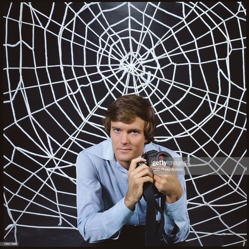 Promotional portrait of American actor Nicholas Hammond, as Peter Parker (whose secret identity is as the costumed superhero Spider-man), as he holds a camera and sits in front a large 'web' for the CBS television series 'The Amazing Spider-Man,' 1978. The series was based on a long-running comic book, developed by Stan Lee and Steve Ditko.