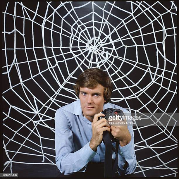 Promotional portrait of American actor Nicholas Hammond as Peter Parker as he holds a camera and sits in front a large 'web' for the CBS television...