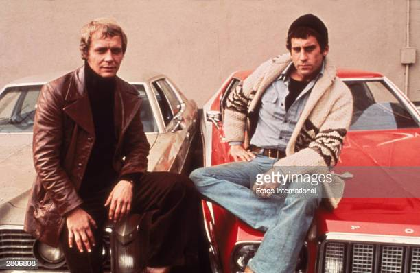 Promotional portrait of American actors David Soul and Paul Michael Glaser sitting on the hoods of their cars from the television series 'Starsky and...