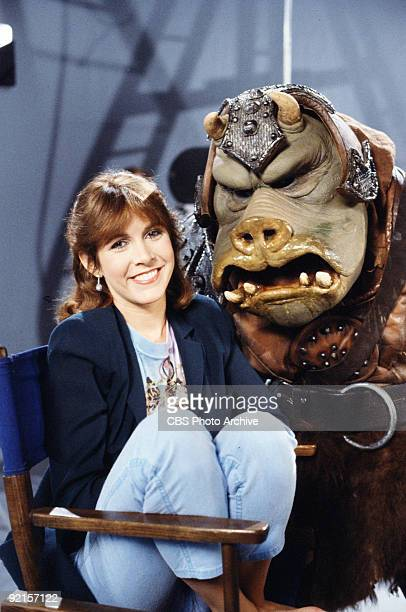Promotional portrait of American actress Carrie Fisher as she poses with a Gamorrean guard on the set of 'Classic Creatures Return of the Jedi' a...