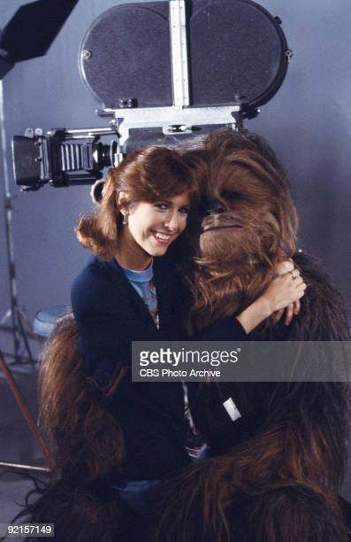 Promotional portrait of American actress Carrie Fisher as she sits on the lap of British actor Peter Mayhew in costume as Chewbacca on the set of...
