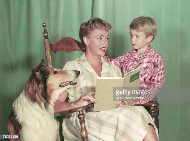 Promotional portrait of American animal actor Baby as Lassie actress June Lockhart as Ruth Martin and Jon Provost as Timmy as they read the book...