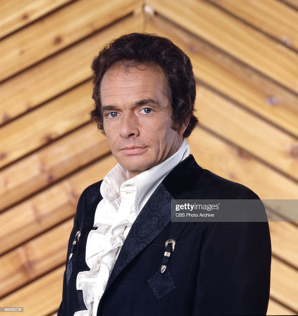 Promotional portrait of American country music singer and guitarist Merle Haggard, as he poses in a brocade jacket and ruffled shirt, 1978.