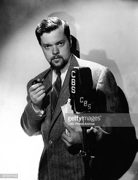 Promotional portrait of American film director actor and screenwriter Orson Welles dressed in a tweed blazer and tie who holds a pipe and papers as...