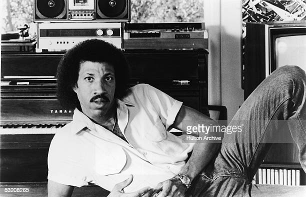Promotional portrait of American rb and pop singer Lionel Richie as he leans on one arm in front of a piano mid 1980s