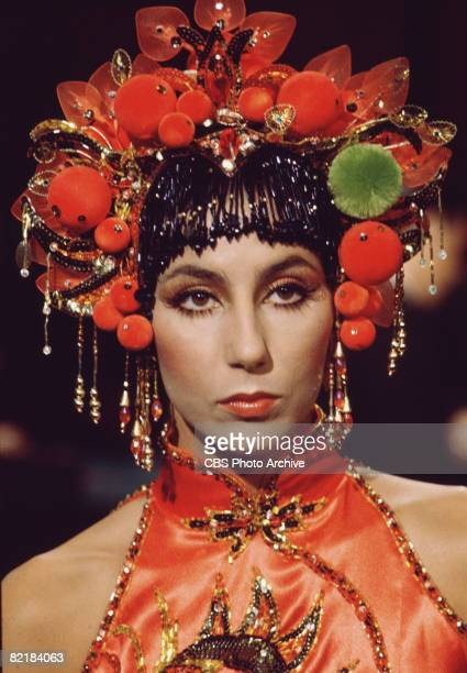 Promotional portrait of American singer and actress Cher in a mock Asianstyled headdress and sleeveless satin top for the television variety show...