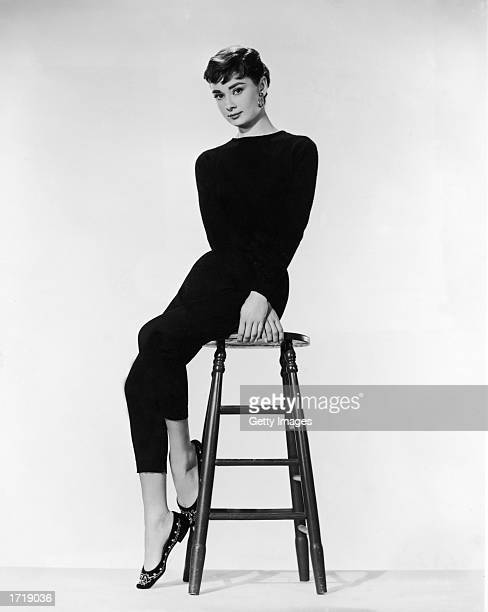 Promotional portrait of Belgianborn actor Audrey Hepburn sitting on a stool and wearing a black pantsuit for the film 'Sabrina' directed by Billy...