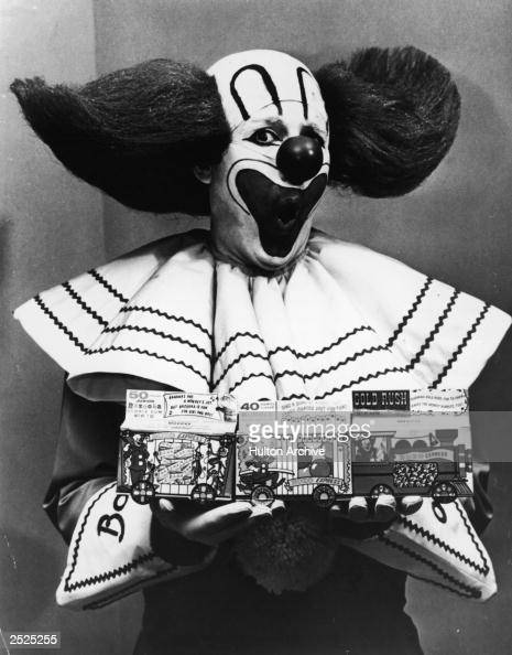 Promotional portrait of Bozo the Clown holding boxes of Bozo Express Bazooka bubble gum with a surprised expression on his face circa 1965