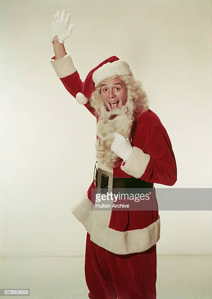Promotional portrait of Cubanborn musician and actor Desi Arnaz who waves as he pulls down the beard of his Santa Claus costume 1950s