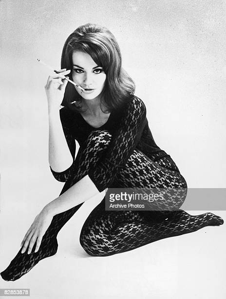 Promotional portrait of French actor Claudine Auger smoking a cigarette in a lace bodysuit for the James Bond film 'Thunderball' directed by Terence...