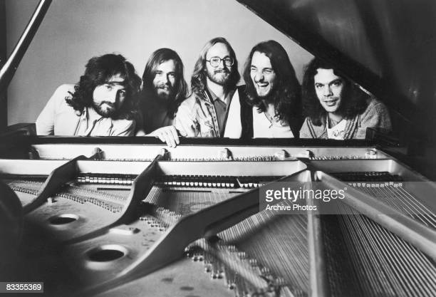 A promotional portrait of rock group Supertramp sitting behind a piano 1970s From left to right Rick Davies Dougie Thomson John Helliwell Roger...