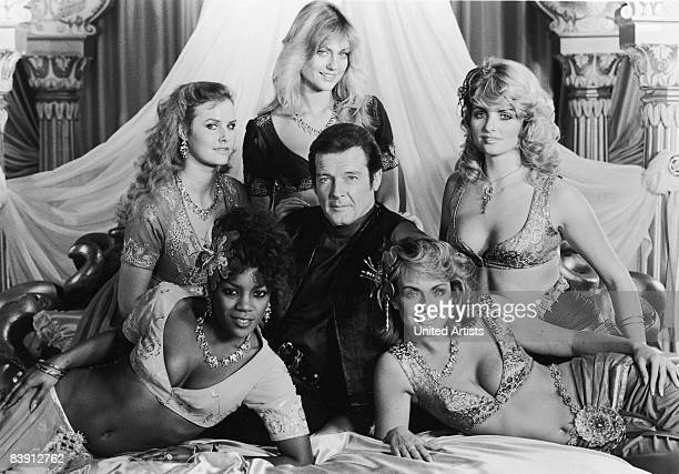 A promotional shot of British actor Roger Moore surrounded by female palace guards in the film 'Octopussy' 1983 Clockwise from top they are Carolyn...