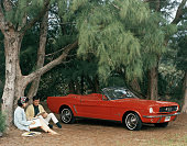 Promotional shot of a red 1964 Ford Mustang convertible parked in a forest clearing with a couple sitting by a pinetree 1964 This first series of the...