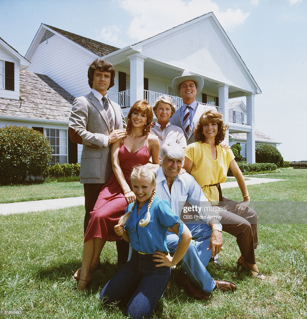 A promotional still from the American television series 'Dallas' shows members of the Ewing family as they pose in front of their television home the...