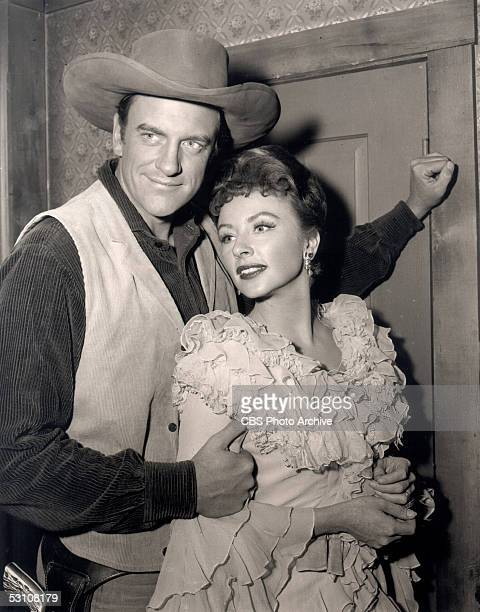 Promotional still of American actors James Arness and Amanda Blake as they embrace and pose in costume from the CBS television western 'Gunsmoke'...