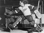 Promotional still of Canadian professional hockey player Roger Crozier goalie for the Detroit Red Wings as he catches a puck while defending the goal...