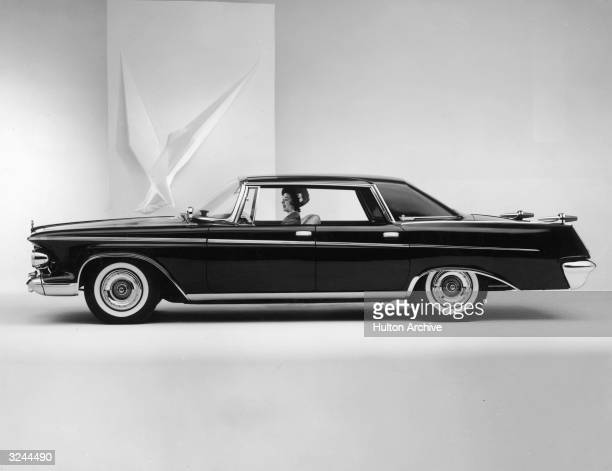 Promotional studio image of a woman sitting in a 1963 Chrysler Imperial LeBaron with the Chrysler logo displayed in the background