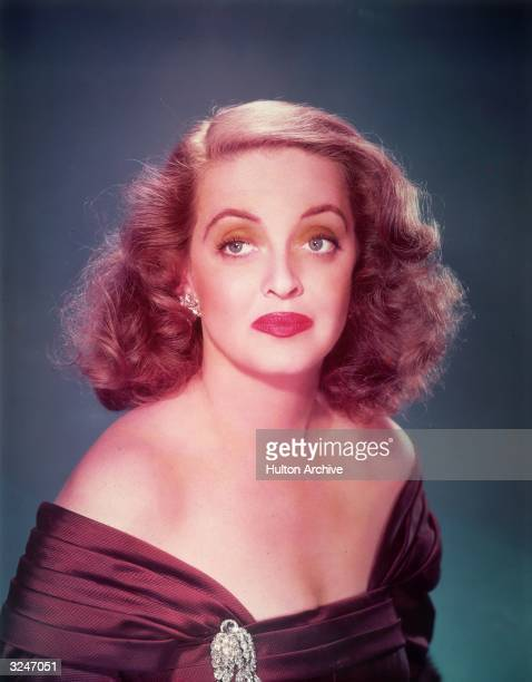 Promotional studio portrait of American actor Bette Davis wearing a violet offshoulder gown with a jeweled brooch against a blue background for...