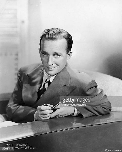 Promotional studio portrait of American singer and actor Bing Crosby holding a pipe with one arm resting on the back of a sofa