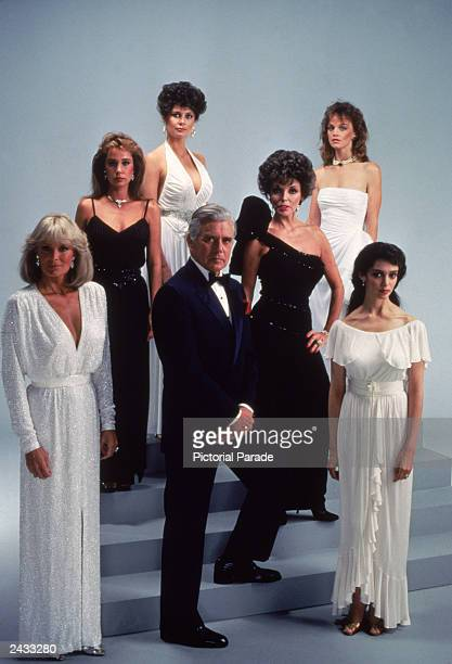 Promotional studio portrait of the cast of the television series 'Dynasty' dressed in white and black evening wear circa 1983 Featuring Linda Evans...