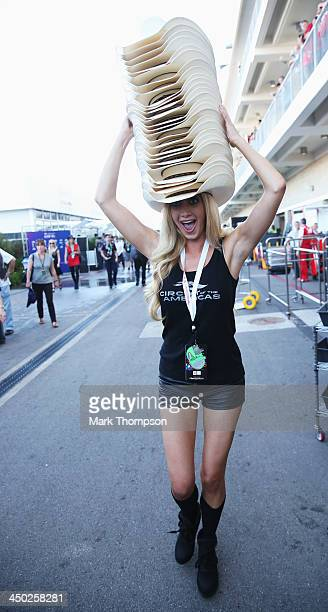 Promotions girl carries a large stack of stetsons through the paddock following the United States Formula One Grand Prix at Circuit of The Americas...