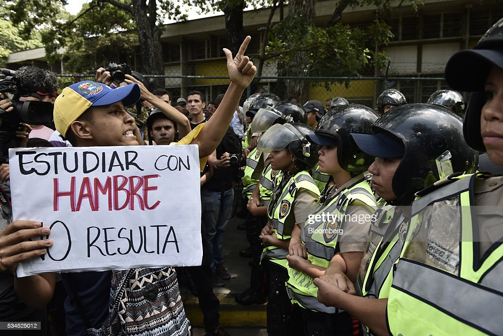 A pro-opposition demonstrator holds a sign next to Bolivarian National Police standing guard that during a march near the Central University of Venezuela in Caracas, Venezuela, on Thursday, May 26, 2016. The opposition is pushing for a recall referendum on President Nicolas Maduro and blame the 53-year-old leader for widespread shortages of food and basic necessities. Photographer: Carlos Becerra/Bloomberg via Getty Images